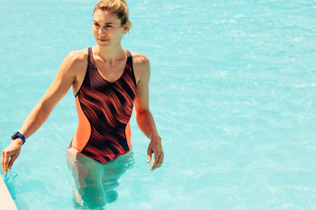 Young woman in swimsuit walking the wading pool. Female in swimwear in the swimming pool. Stock Photo - 120521139