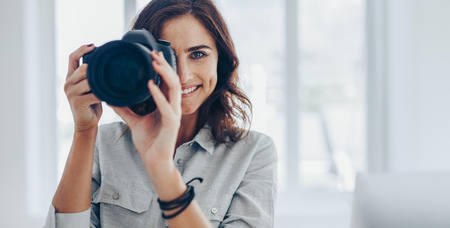 Happy young woman taking pictures with her DSLR camera indoors. Professional photographer taking photos in her studio.