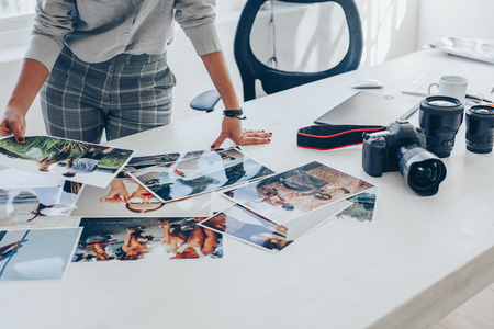 Woman standing at her desk and choosing the best images from photoshoot. Female photographer looking at the photo prints on table. Imagens