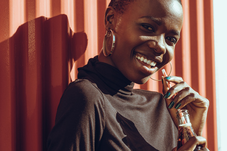 Close up of beautiful young woman standing outdoors and looking at camera while drinking cola. African woman relaxing outdoors on a summer day.