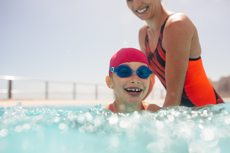 Girl getting swimming lesson in a outdoor pool with her mother. Girl wearing swim cap and goggles learning to swim with mothers help.