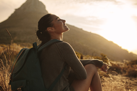 Woman sitting on ground smiling with her eyes closed. Caucasian female tourist taking a break after hiking on country trail.