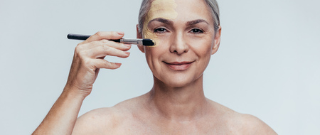 Beautiful senior woman applying foundation on her face with a makeup brush. Elder woman applying liquid foundation against grey background.