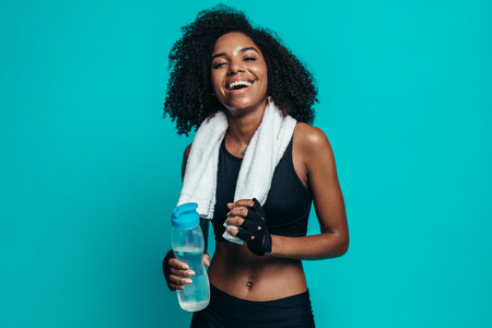 Cheerful young woman with water bottle and towel around neck on blue background. Healthy young female taking a break after exercising