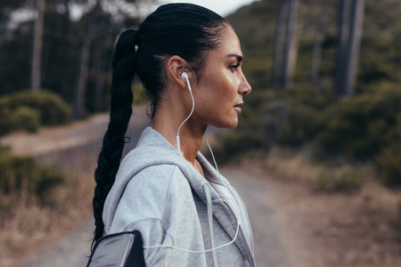 Side view of young woman with earphones standing outdoors after morning run. Female taking a rest after outdoor workout.