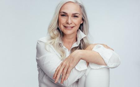 Bella donna matura seduta su sfondo bianco. Senior donna seduta rilassata in studio.