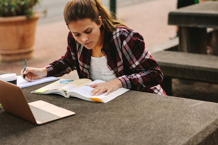 Female student sitting at college campus and making notes. Woman student studying at university campus with a laptop in front.