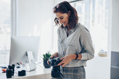 Female photographer working in her office. Woman photographer checking pictures on camera and smiling. Stockfoto