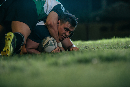Rugby player being blocked by opposite team players. Sports men pins down opponent during rugby match at night.