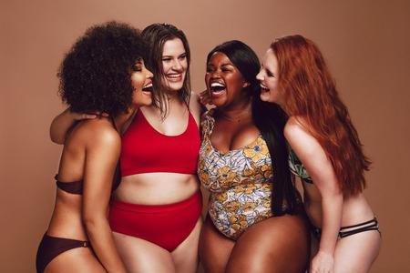 Mujeres multiétnicas en traje de baño divirtiéndose juntas en el estudio.
