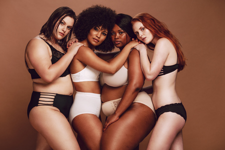 Gruppe von Frauen unterschiedlicher Größe in Dessous, die sich umarmen und in die Kamera schauen. Diverse Gruppe von Frauen in verschiedenen Unterwäsche zusammen auf braunem Hintergrund.