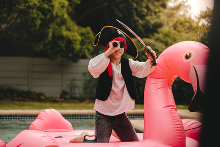 Small boy dressed up as pirate standing on a inflatable flamingo mattress in the pool. Boy pretending to be a pirate in the swimming pool.
