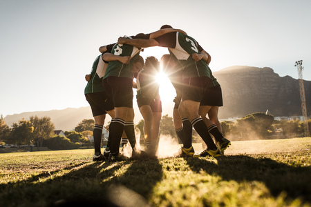 Rugby-Team steht in einem Huddle und reibt ihre Füße auf dem Boden. Rugby-Team feiert Sieg.