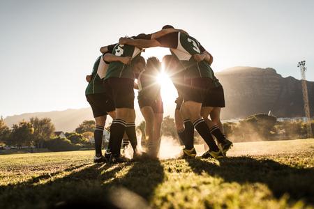 Squadra di rugby in piedi in un huddle e strofinando i piedi a terra. Squadra di rugby che celebra la vittoria.
