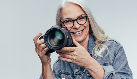 Senior woman photographer holding a DSLR camera. Smiling female photographer taking pictures with professional camera. 写真素材 - 120521749