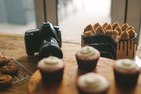 Digital camera on table with freshly made cakes, cookies and cupcakes on wooden table. Dslr camera with pastry items on a table. 写真素材