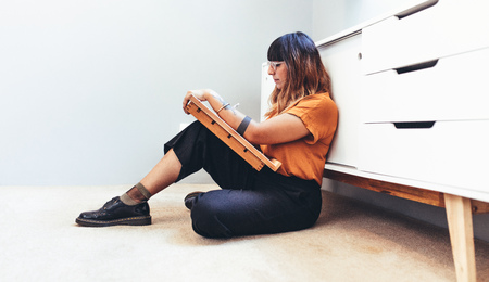 Side view of a female creative artist sitting on floor and making a drawing. Illustrator working on her designs sitting comfortably on floor.