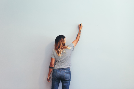 Illustrator making a sketch on a wall. Rear view of a female creative artist writing on a wall .