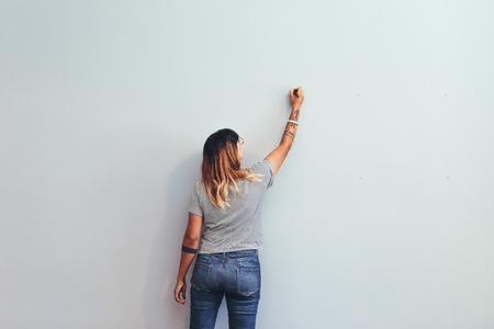 Ilustrador haciendo un boceto en una pared. Vista trasera de una artista creativa femenina escribiendo en una pared.