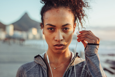 Close up of woman athlete wearing earphones outdoors. Female listening to music during workout. Фото со стока