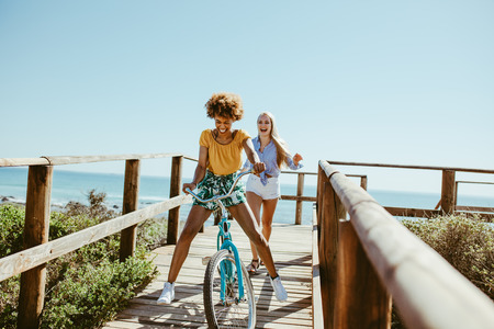 Cheerful woman riding a bicycle on boardwalk with friend running at the back. Female friends enjoying on vacation. Stock Photo
