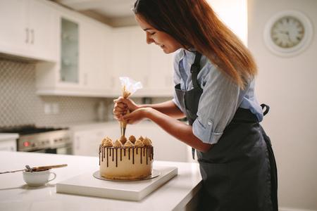 Köchin, die Kuchen mit Schlagsahne mit Partytasche dekoriert. Frau in der Schürze, die zu Hause einen köstlichen Kuchen zubereitet. Standard-Bild