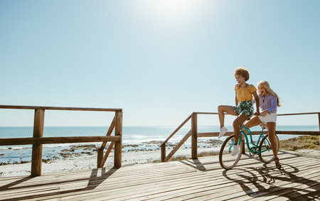 Joyful young women riding a bicycle together. Best friends having fun on a bike at the seaside boardwalk. Stock Photo