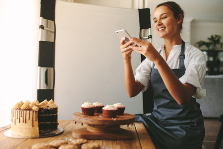 Happy woman chef taking a picture of pastries on a wooden board with smart phone while standing at the kitchen. Female baker taking pictures of the dessert for her food blog. Standard-Bild