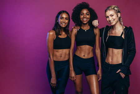 Multi-ethnic fitness women together against colored background. Diverse group females in sportswear after workout. Banco de Imagens