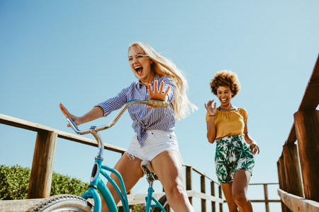 Excited girl cycling on a boardwalk with her friends running. Two woman friends enjoying themselves on the vacation.