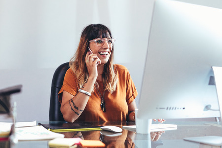 Smiling businesswoman talking on mobile phone while looking at a computer. Cheerful entrepreneur working in office sitting at her desk. Banco de Imagens