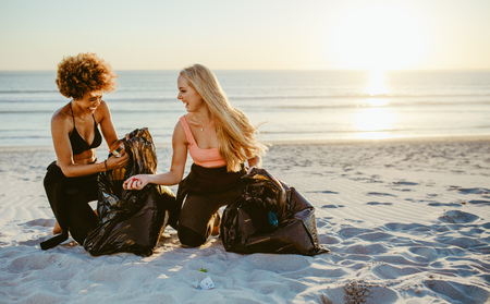 Two female volunteers gathering garbage from the beach. Female surfers with garbage bags cleaning sandy seashore area.