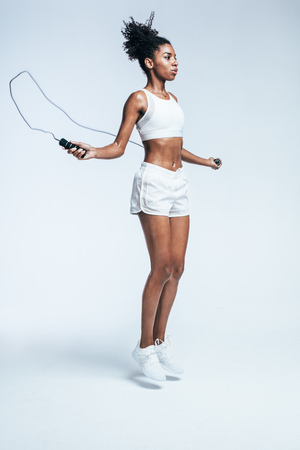 Healthy young woman skipping rope in studio. Muscular young woman exercising with jumping rope on white background.