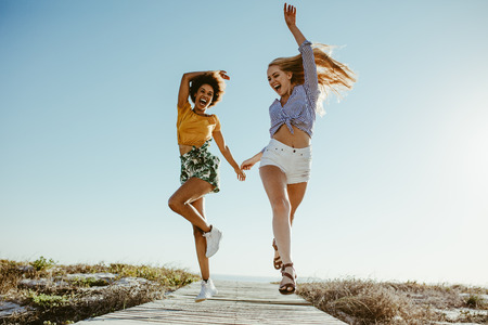 Two excited female friends running with joy on boardwalk along the beach. Two women enjoying themselves on vacation.