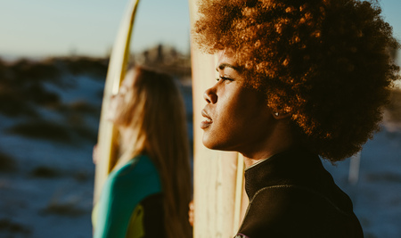Close up of young african woman holding a surfboard and looking at the sunset with her friend standing at the back. Two women surfers on the beach at sunset. Stock Photo
