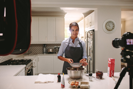 Woman preparing cake in the kitchen and recording video on a camera. Pastry chef recording content for the food vlog.
