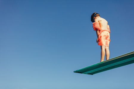Low angle shot of boy with sleeves floats on diving board preparing for dive in the pool. Boy standing on diving spring board against sky. Stockfoto
