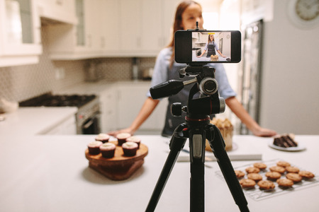 Young female blogger recording video on mobile phone camera in kitchen.