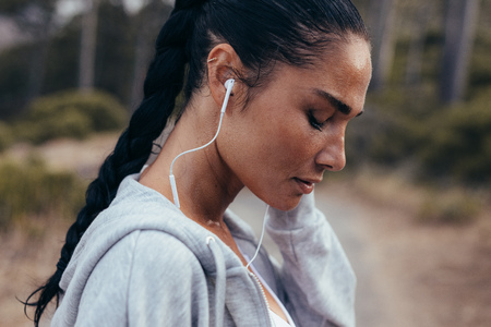 Side view of a female athlete wearing earphones listening to music. Sportswoman listening to music outdoors in morning.