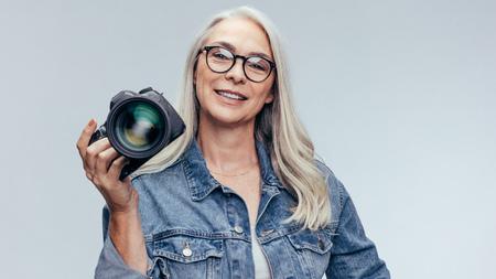 Senior professional photographer holding a DSLR camera.