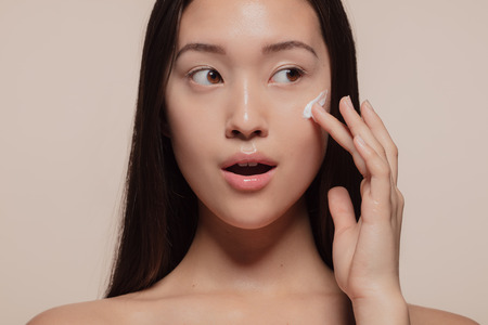 Close up of a asian female model applying moisturizer to her face and looking away. Woman applying moisturizer cream on her pretty face against beige Stockfoto