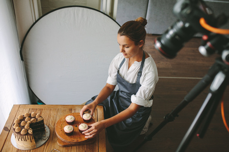 Young woman wearing apron arranging cupcake on the table with a camera recording the video content. Stock Photo