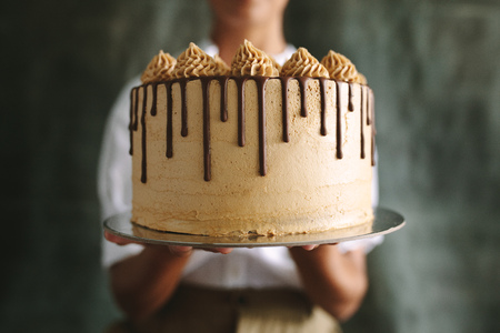 Close up of female chef holding cake. Baker showing a tasty cake against gray Standard-Bild
