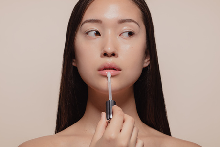 Portrait of beautiful young woman applying transparent lip gloss with applicator. Asian female model looking away while doing make up against beige background. 免版税图像 - 121031422