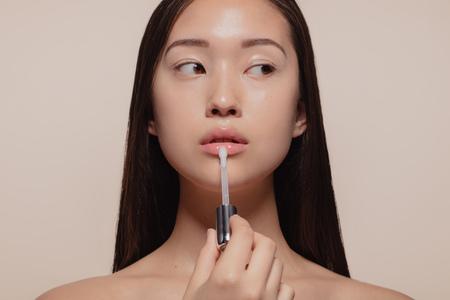 Ritratto di bella giovane donna che applica lucidalabbra trasparente con applicatore. Modello femminile asiatico che guarda lontano mentre si trucca su sfondo beige.