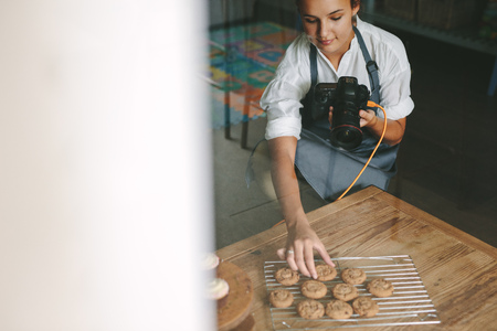 Female chef inside a kitchen arranging the cookies on the grill with digital camera in hand.
