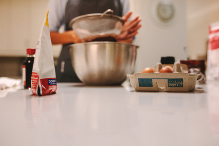 Baking ingredients on kitchen counter with woman sifting flour in the bowl. Pastry chef preparing cake in kitchen.