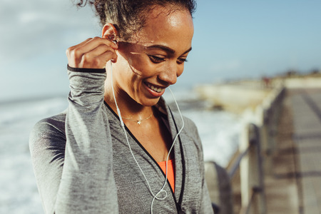 Healthy young woman listening to music while exercising at the promenade. Female runner adjusting the earphones and smiling while taking a break from the running workout.