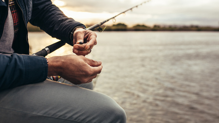 Close up of a person sitting beside a lake getting ready to catch a fish with his fishing rod. Cropped shot of a man sitting near a lake fixing a bait to his fishing rod.