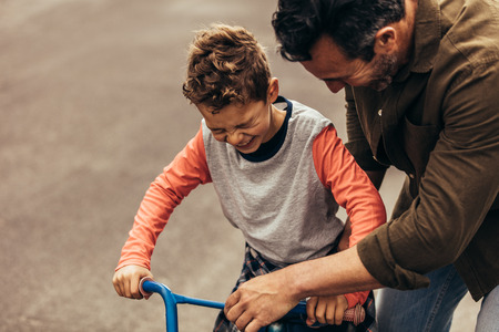 Man holding the bicycle while his son learns to ride it. Boy excited to ride a bicycle. Imagens